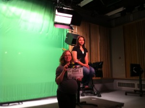 Allie Verbovetskaya (Instructional Technologies Librarian; seated) and Jennifer King (Science Librarian) posing in front of the green screen before 'Action!' is called